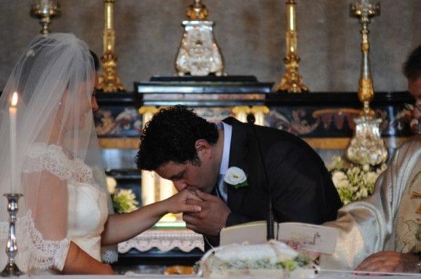 Lo sposo bacia l'anello alla sposa.