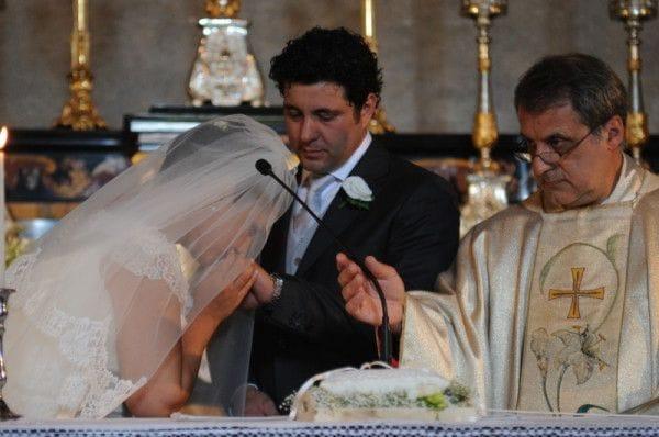 La sposa bacia l'anello allo sposo.